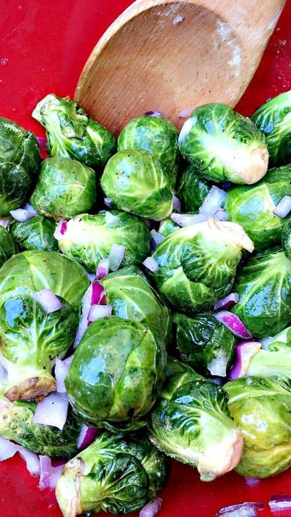 close up of red bowl with brussels sprouts and onions and a wooden spoon