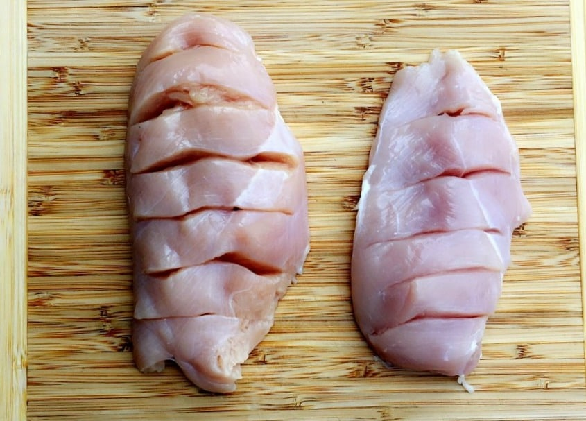 raw chicken breasts with slits cut into the top