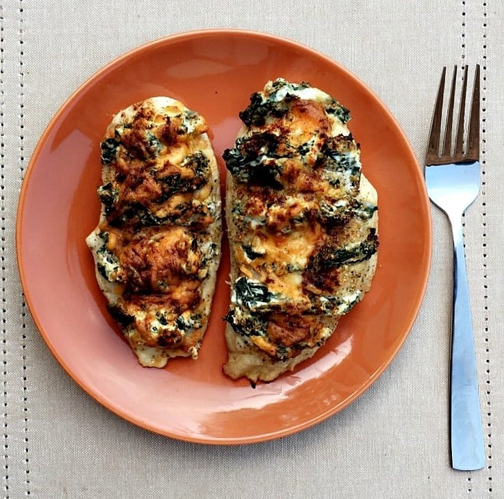 spinach and cream cheese stuffed chicken on an orange plate