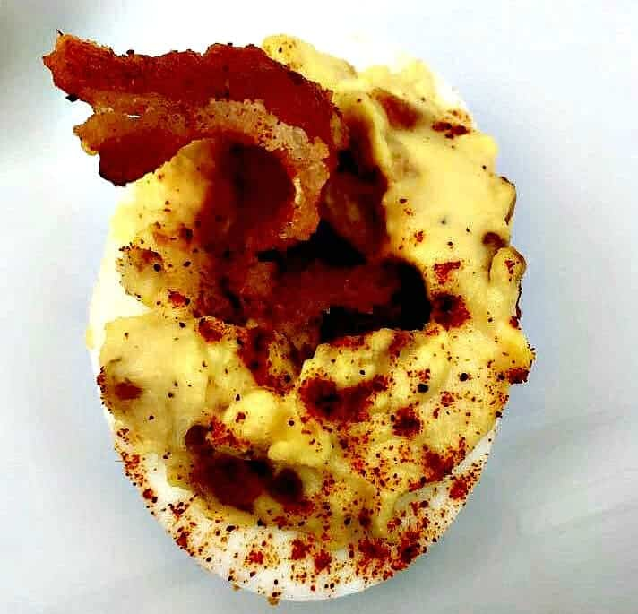 close up of bacon deviled egg on a white plate