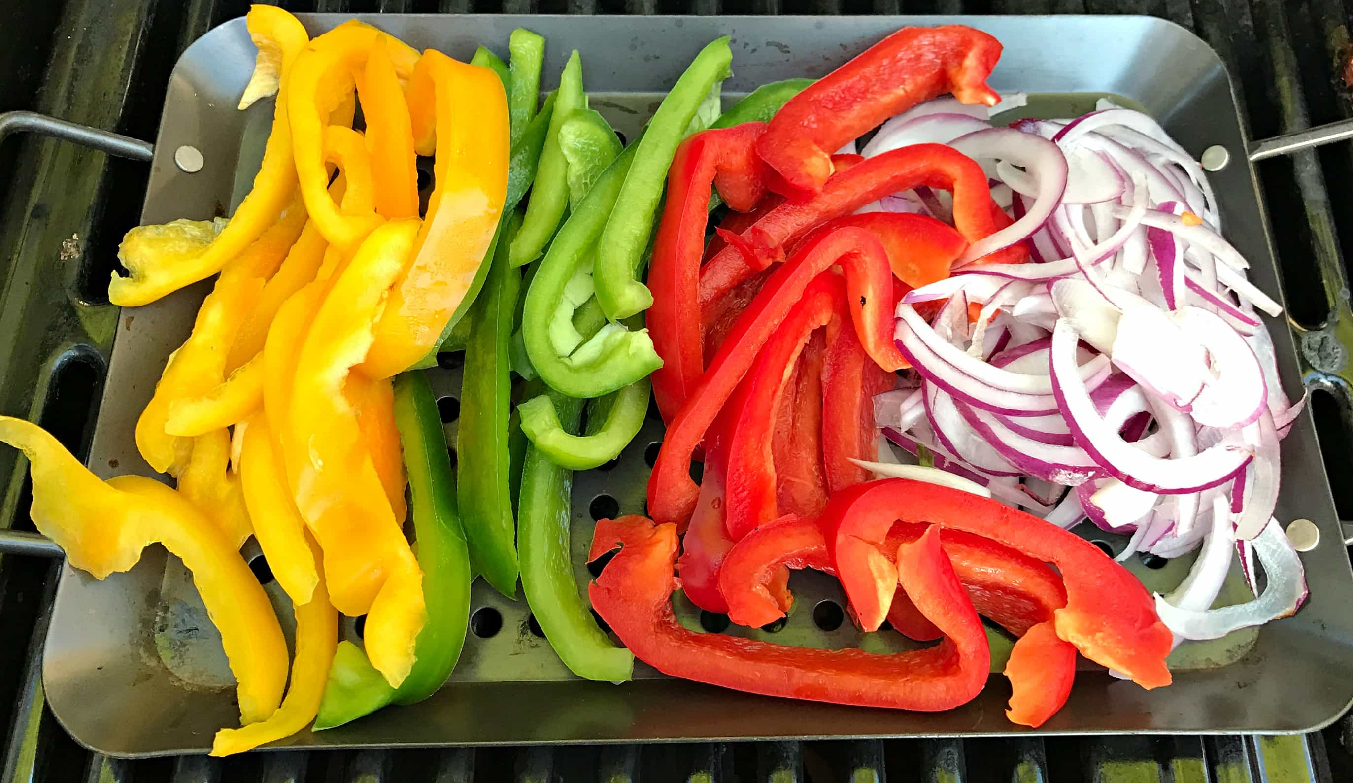 sliced bell peppers and purple onion on a grill tray