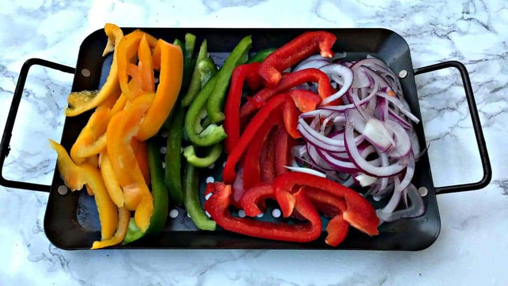sliced bell peppers and onions on a grill tray