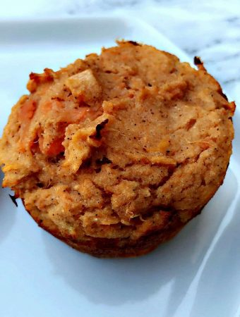 close up of two baked sweet potato protein muffin on a white plate