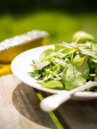bowl of salad greens and bottle of olive oil on a wooden picnic table