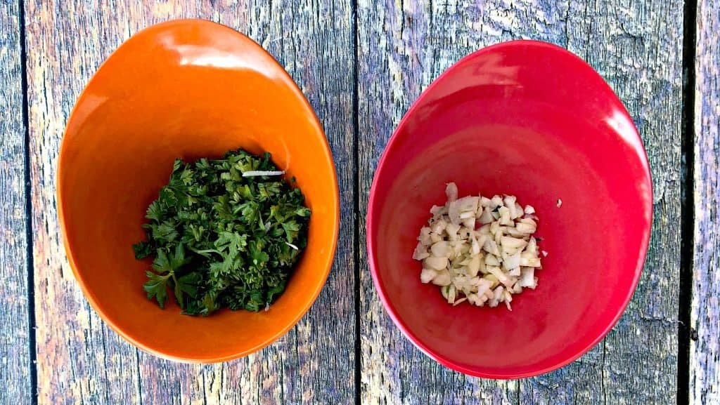 parsley and garlic in red and orange bowls