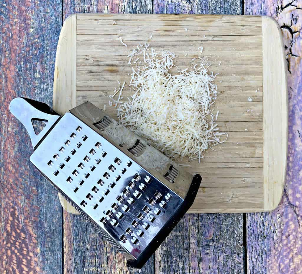 parmesan cheese with a cheese grater on a cutting board
