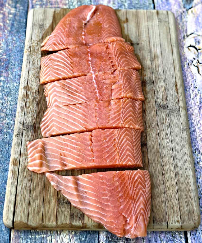 raw salmon sliced on a cutting board