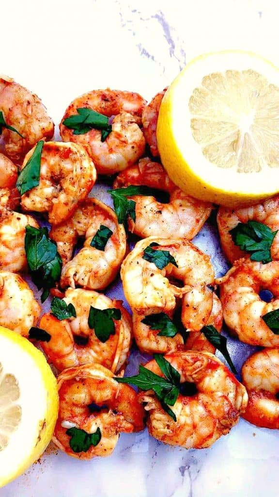 spicy smoky shrimp on a white surface with a lemon