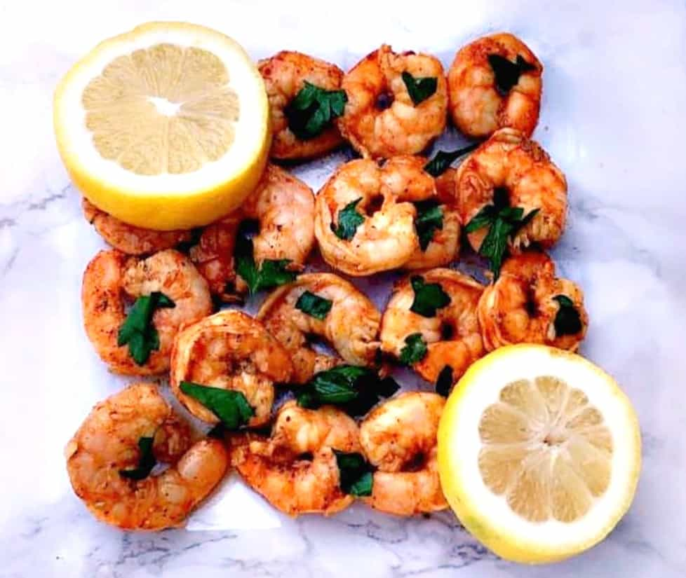 spicy smoky shrimp on a white surface with sliced lemons