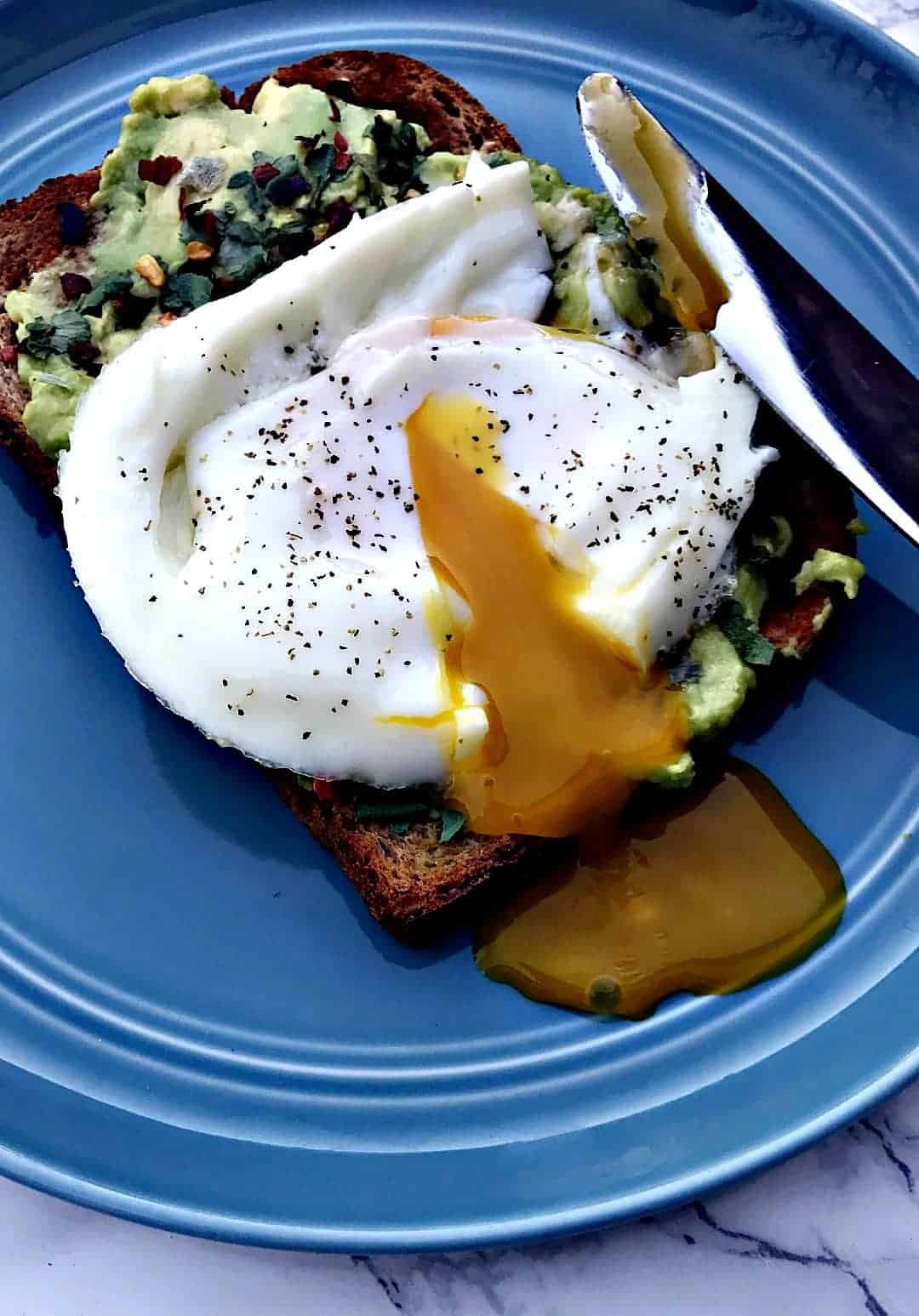 avocado cilantro lime toast with a poached egg on a plate