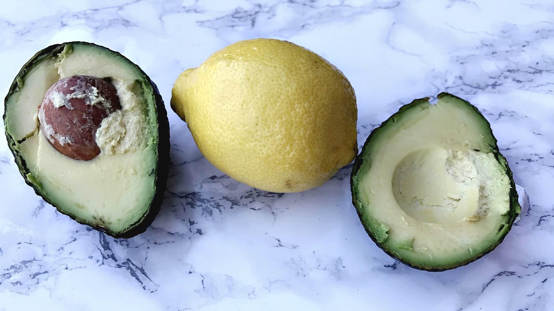 sliced avocado and a lemon on a counter top