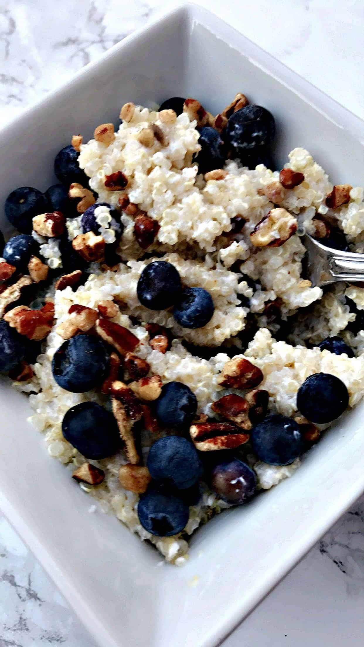 blueberry quinoa breakfast bowl with pecans in a white bowl