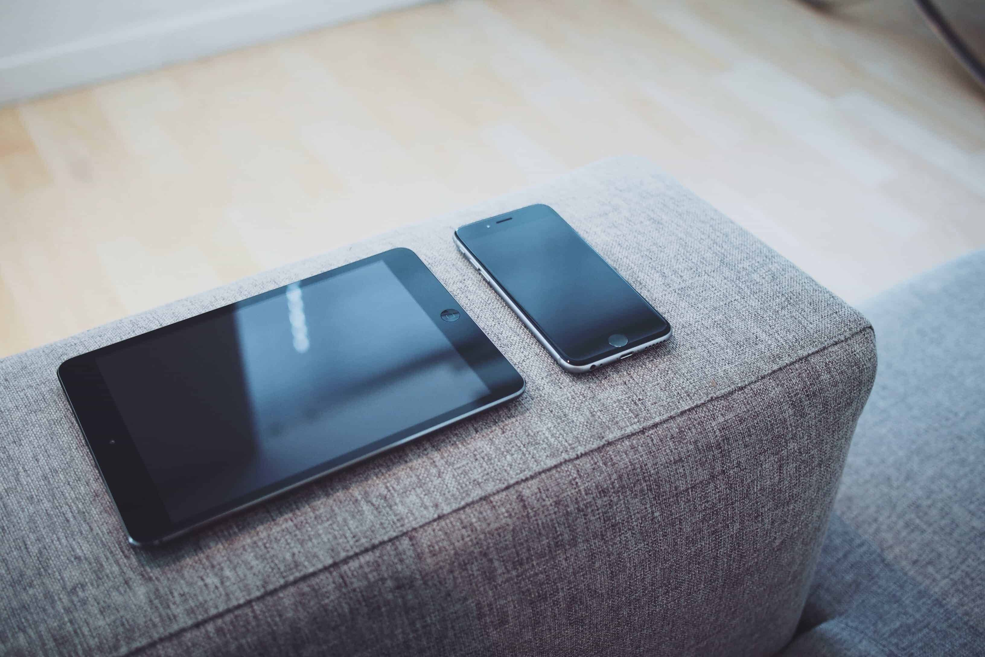 picture of an iPad and iPhone on the arm of a sofa