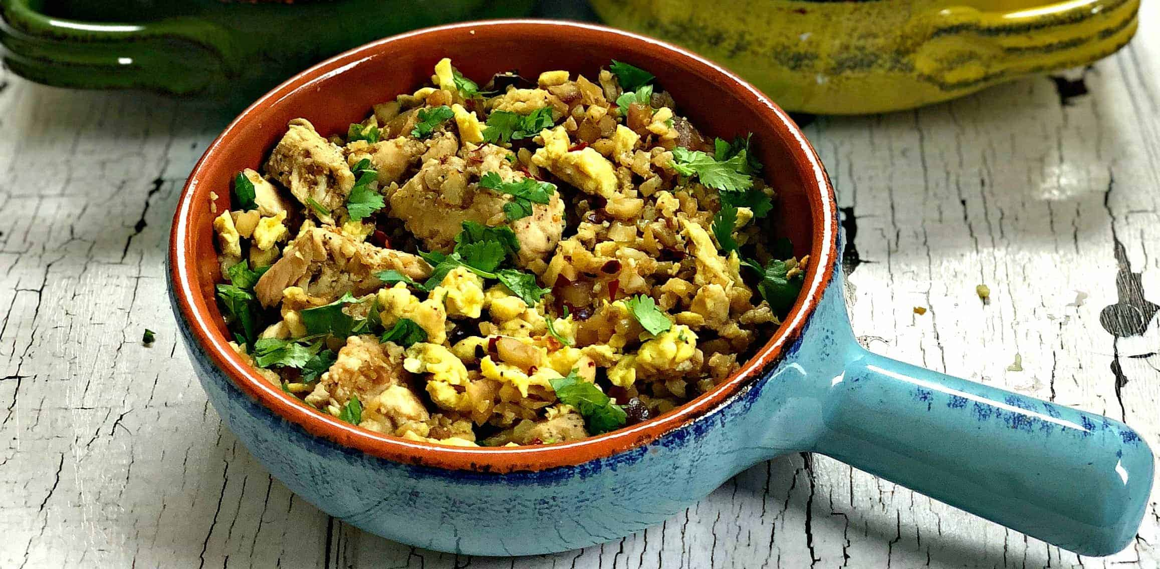 Low-Carb Paleo Cauliflower Vegetable Fried Rice with Chicken in a serving dish