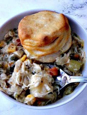 bowl of crock pot chicken pot pie and roll