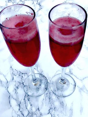 2 champagne flutes filled with raspberry sorbet mimosas