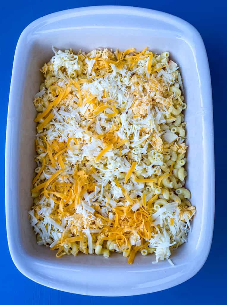 bacon gouda macaroni and cheese in a baking dish with shredded cheese