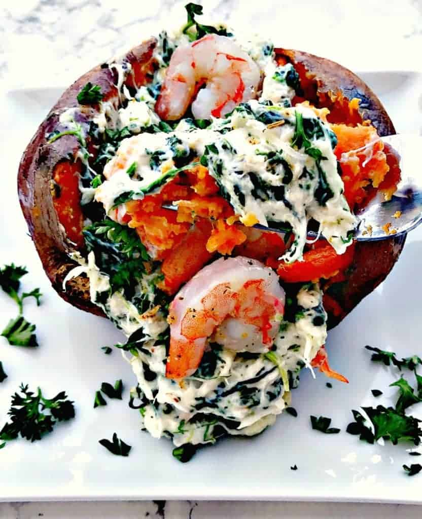 sweet potato stuffed with spinach, crab and shrimp on a white plate