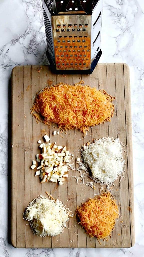 a cheese grater and a cutting board with assorted shredded cheeses on the cutting board
