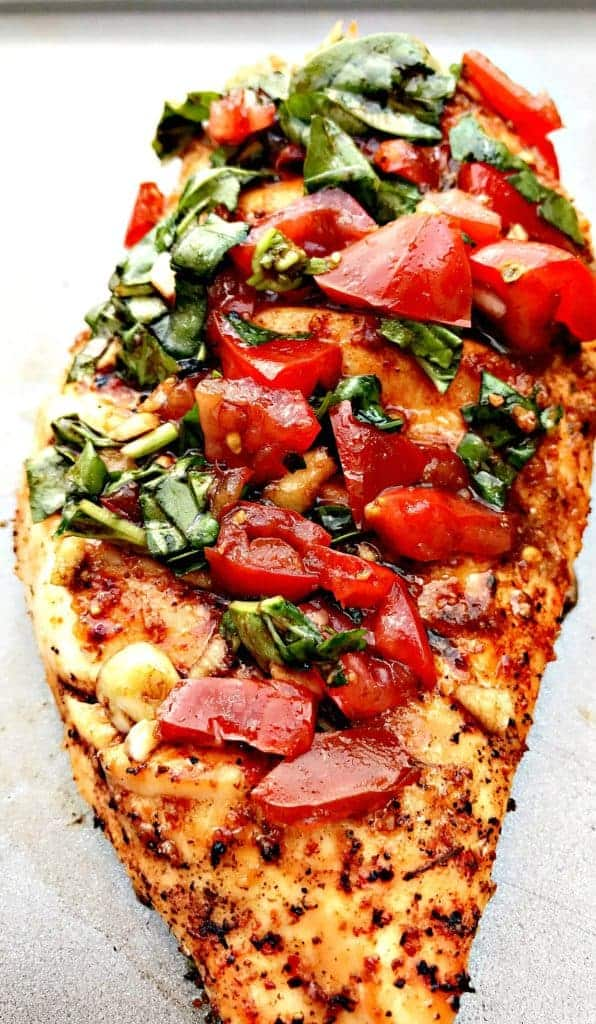 close up of bruschetta stuffed chicken on a baking sheet