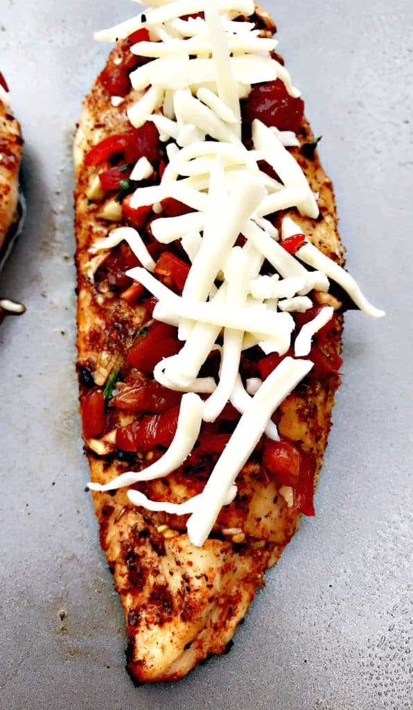 close up of bruschetta stuffed chicken with shredded cheese on a baking sheet