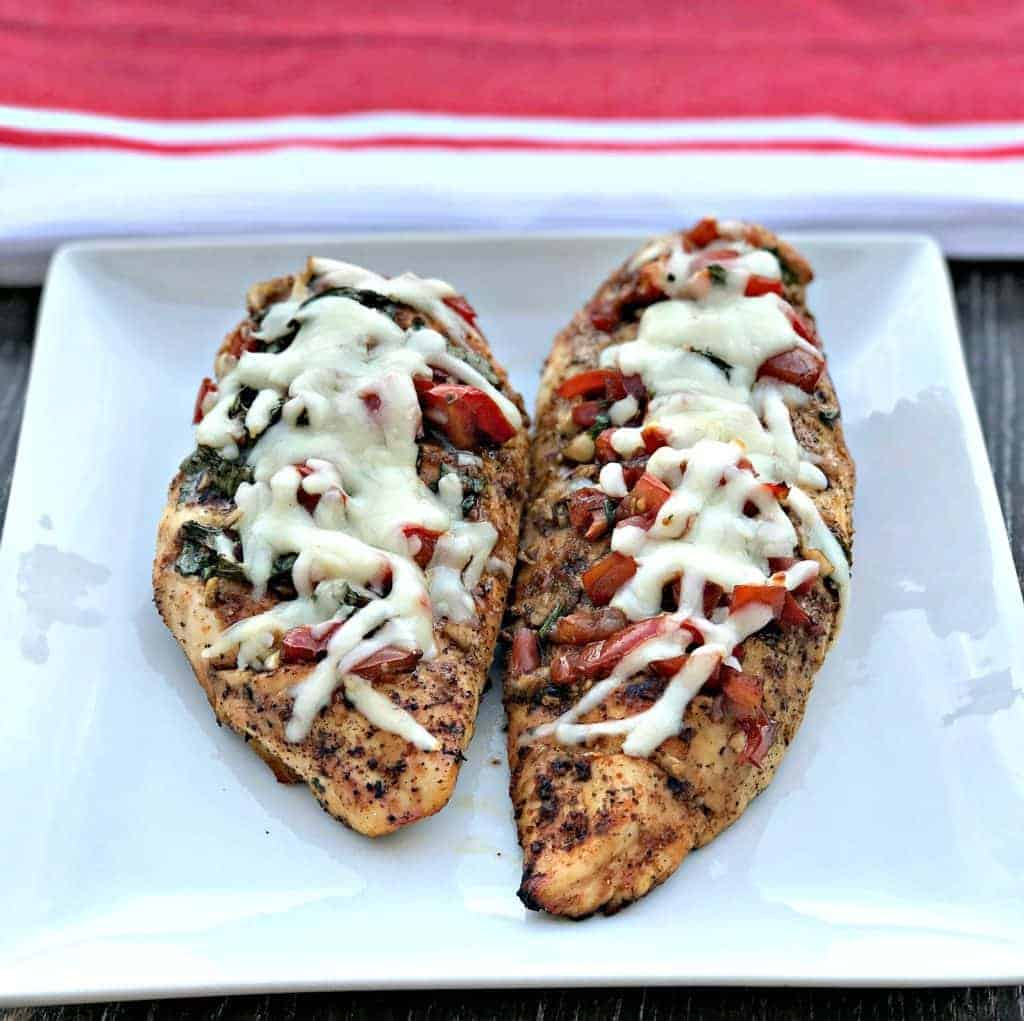bruschetta stuffed chicken on a white plate with a red and white napkin