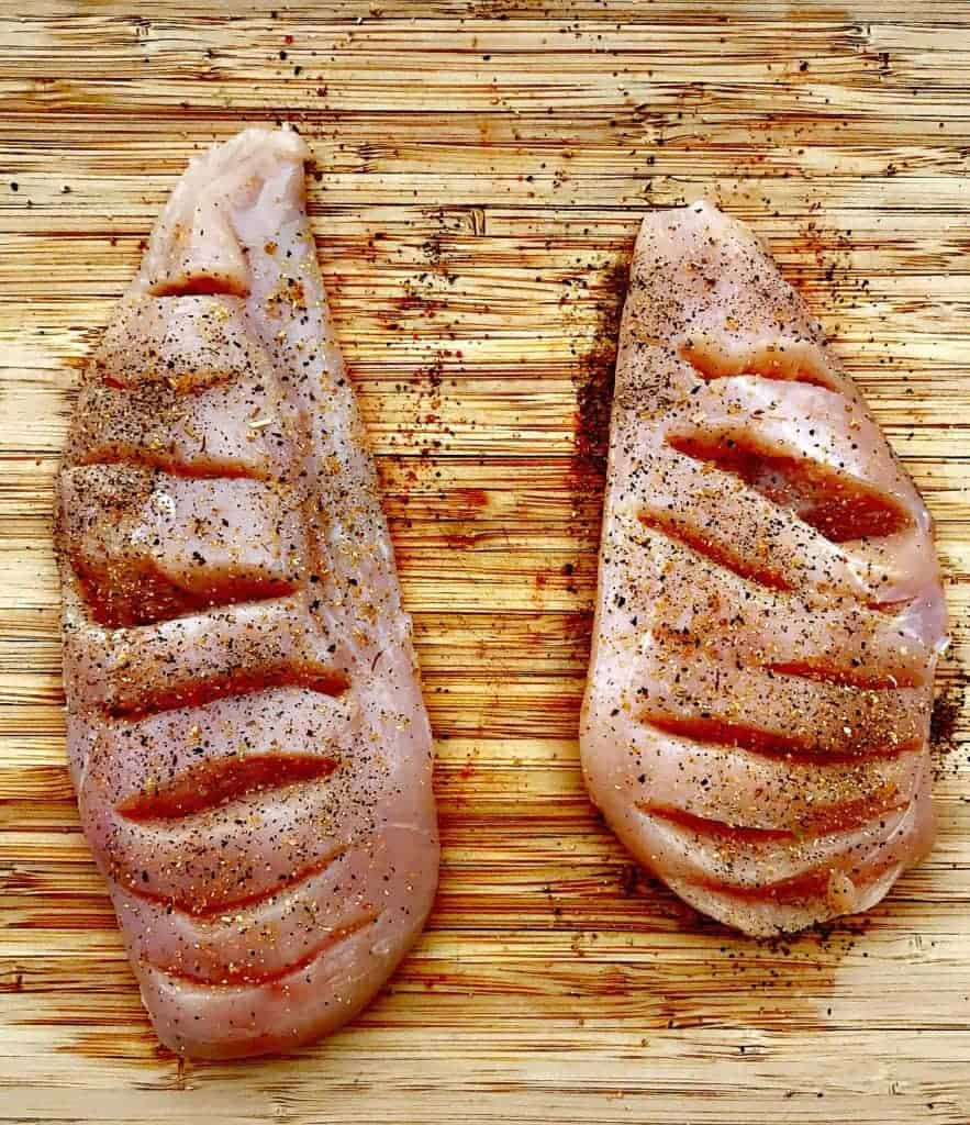 raw chicken breasts on a cutting board sliced for stuffing