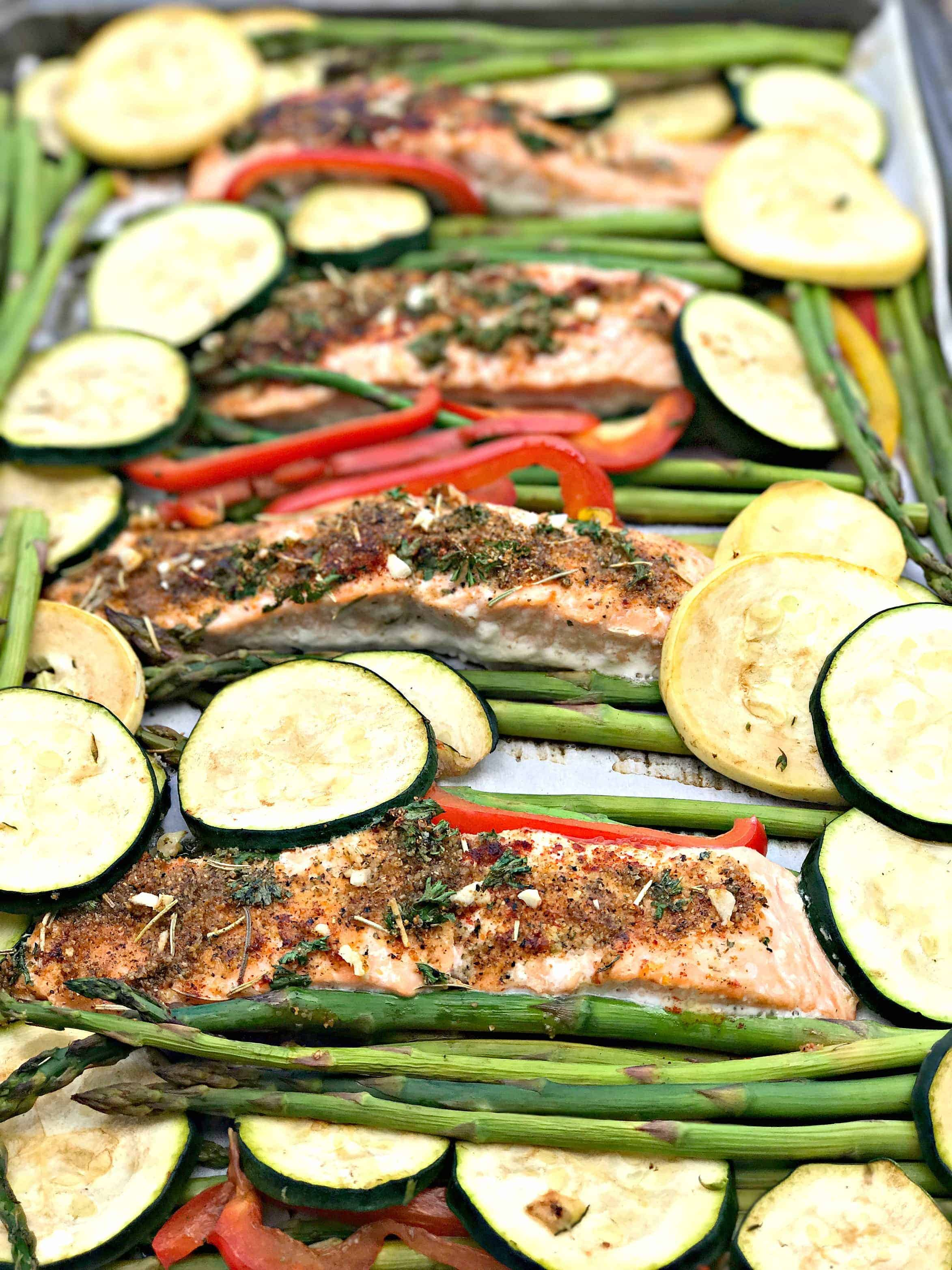 a baking sheet with 4 salmon fillets seasoned with herbs and sliced zucchini and squash and asparagus