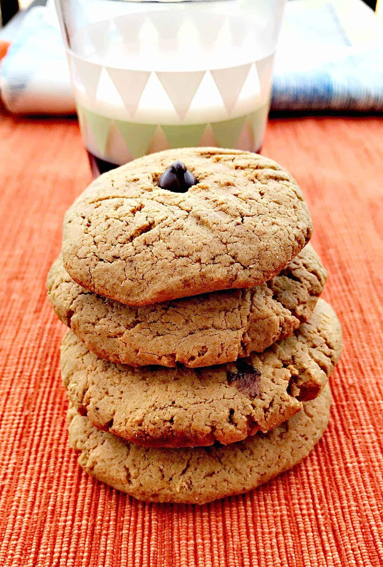 4 peanut butter dark chocolate chip protein cookies stacked in front of glass of milk