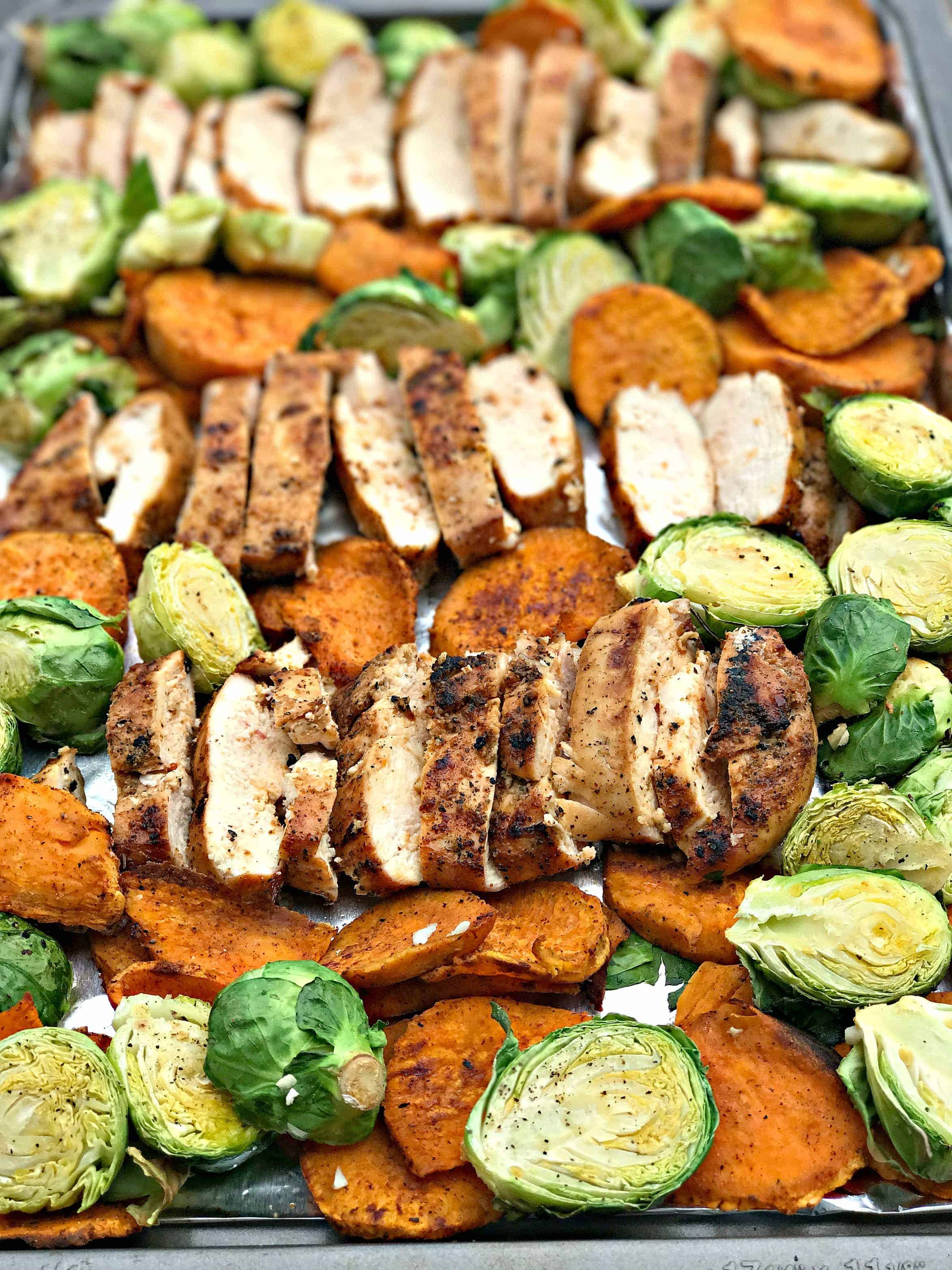 sliced chicken breasts, sweet potatoes, brussels sprouts on a baking sheet