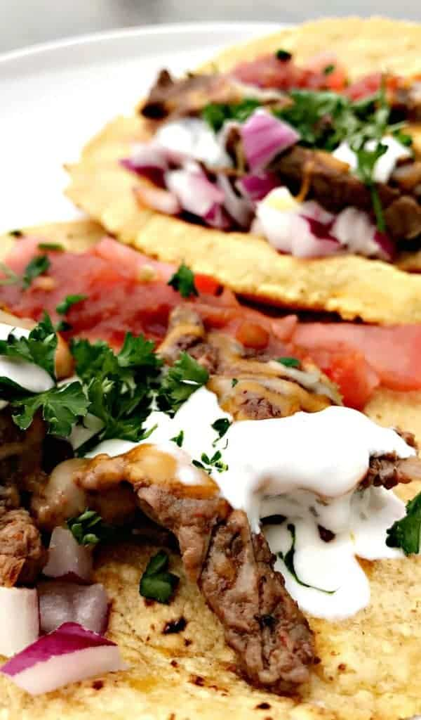 close up Instant Pot 10-Minute Steak Tacos (carne asada) with sour cream and tomatoes