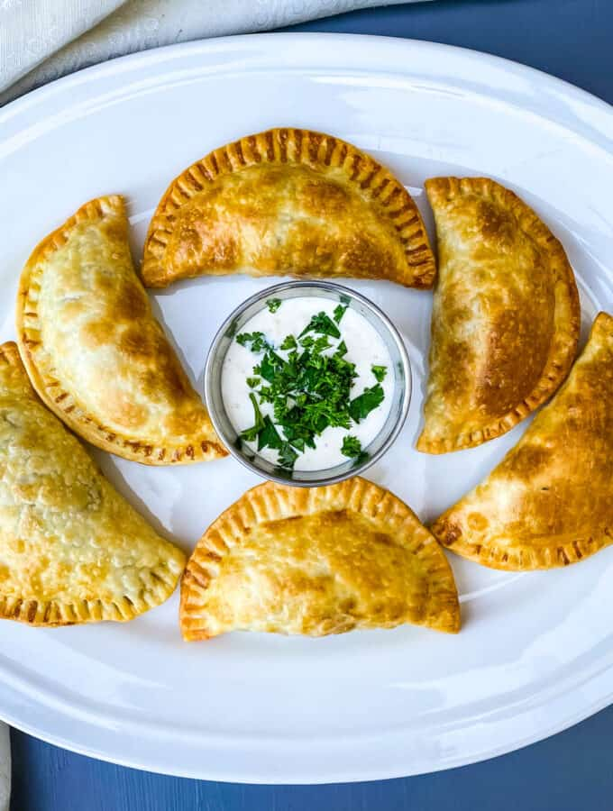 beef empanadas on a white plate with white sauce and cilantro