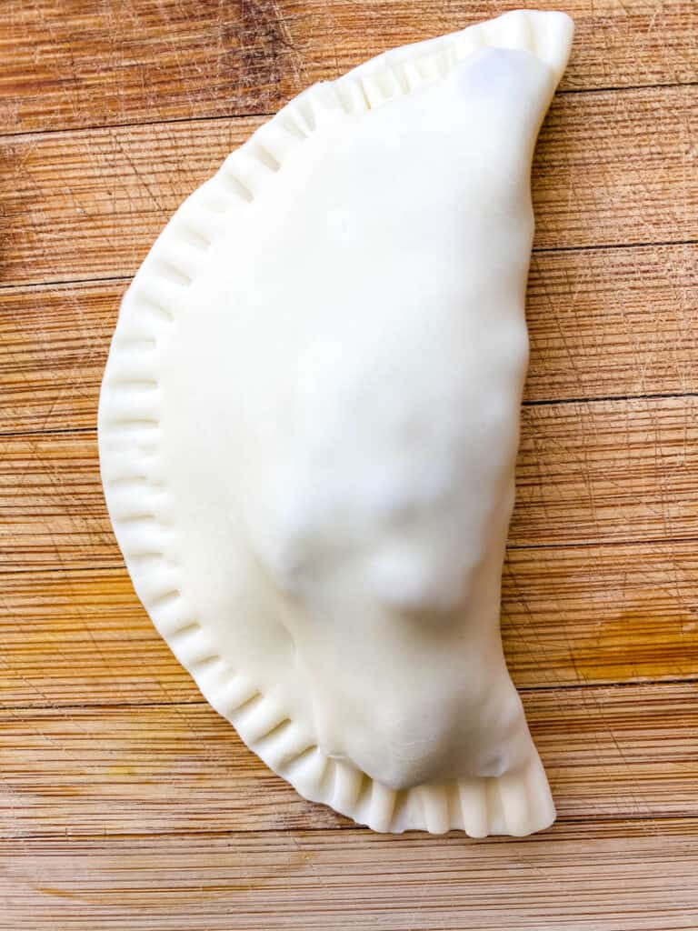 uncooked beef empanada on a bamboo cutting board