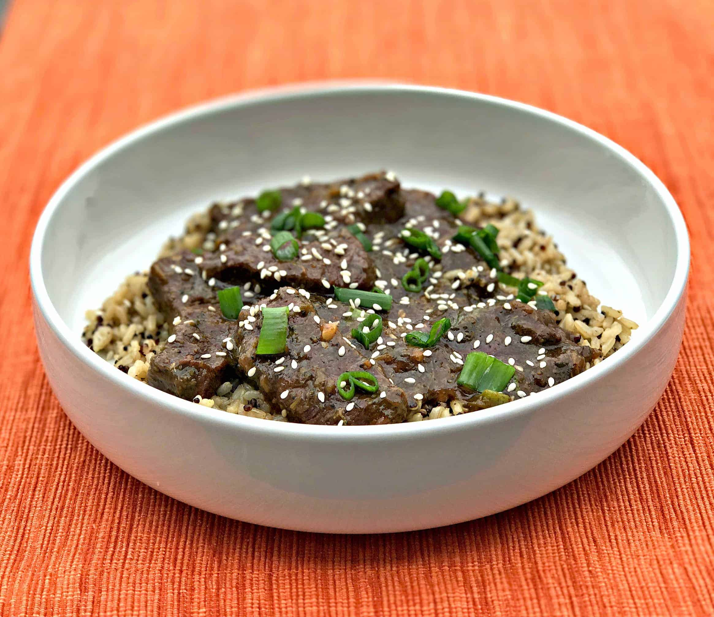 mongolian beef, quinoa and brown rice in a white bowl