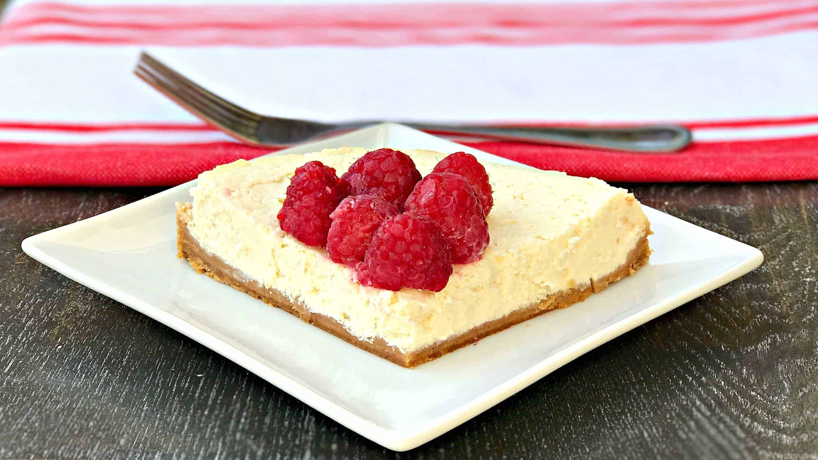 cheesecake topped with raspberries on a white plate