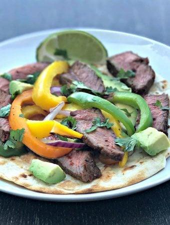 grilled steak fajitas on a tortilla on a white plate