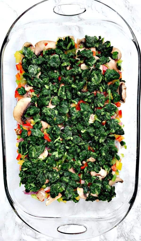 vegetable ingredients for Low-Carb Bacon, Egg, and Spinach Breakfast Casserole in a glass pan