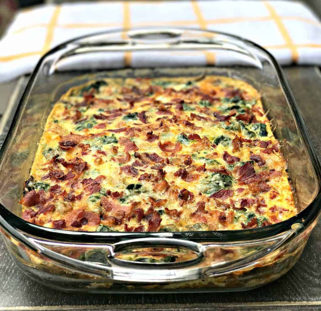 Low-Carb Bacon, Egg, and Spinach Breakfast Casserole in a glass pan with a white and yellow napkin