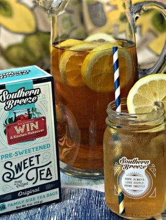 glass pitcher filled with sweet tea lemon bourbon cocktail, package of sweet tea tea bags, mason jar with sweet tea lemon bourbon cocktail with a slice of lemon