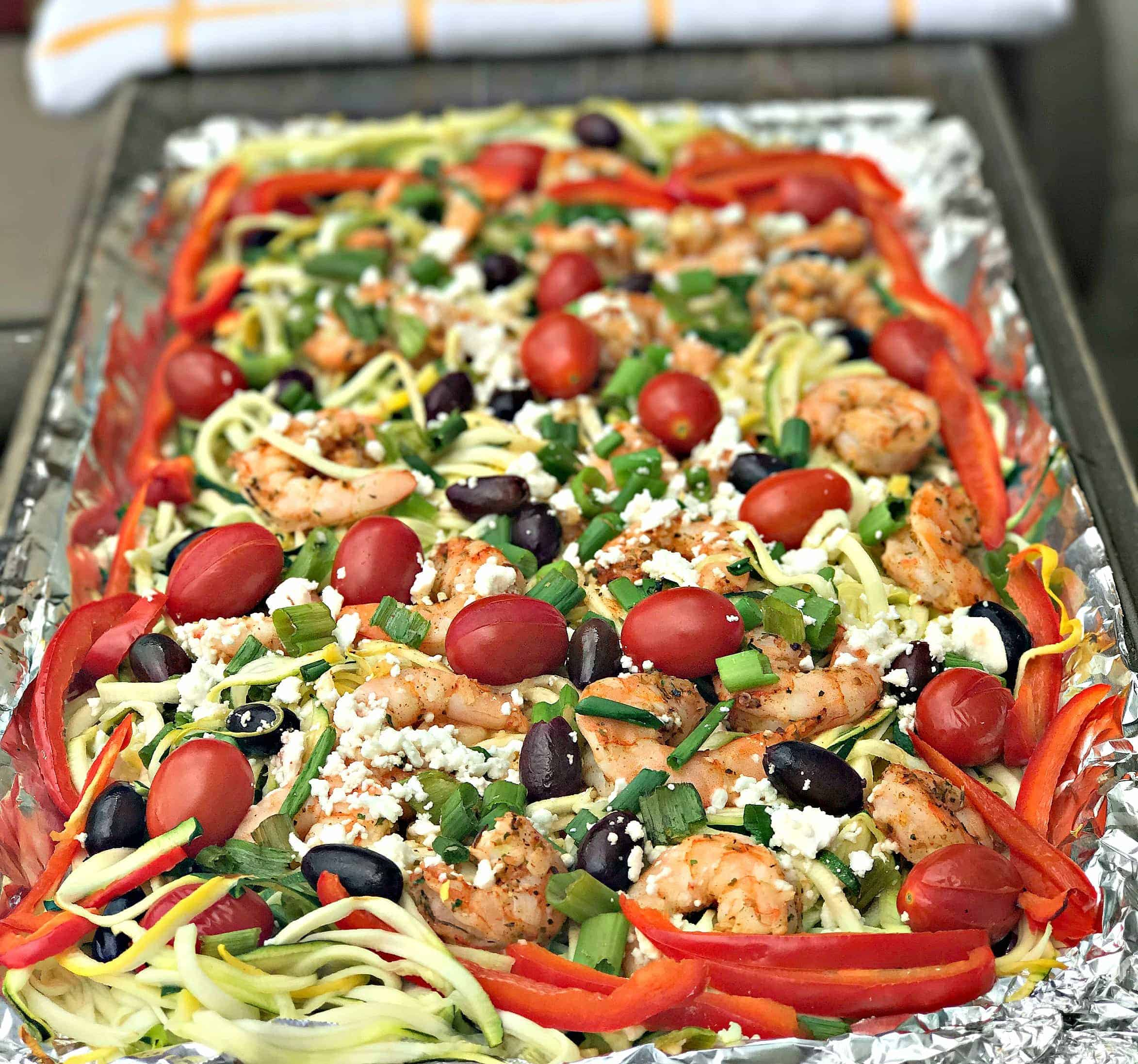 Mediterranean shrimp with zucchini noodles on a foil lined baking sheet