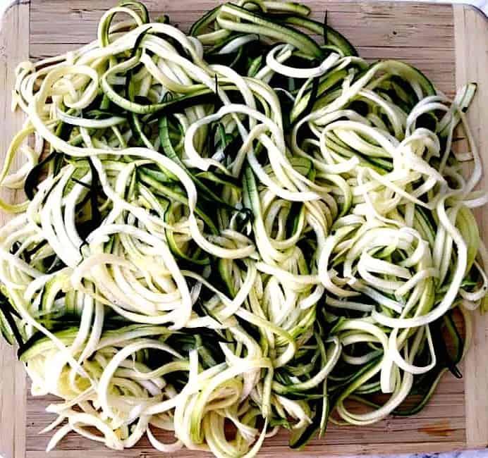 spiralized zucchini noodles on a cutting board