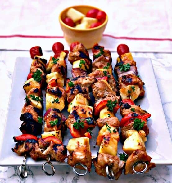 hawaiin pineapple chicken kabob skewers on a white plate
