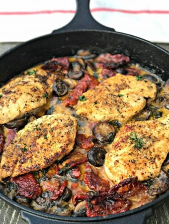 Chicken with Sun-Dried Tomatoes and Mushrooms in White Wine Cream Sauce in a skillet
