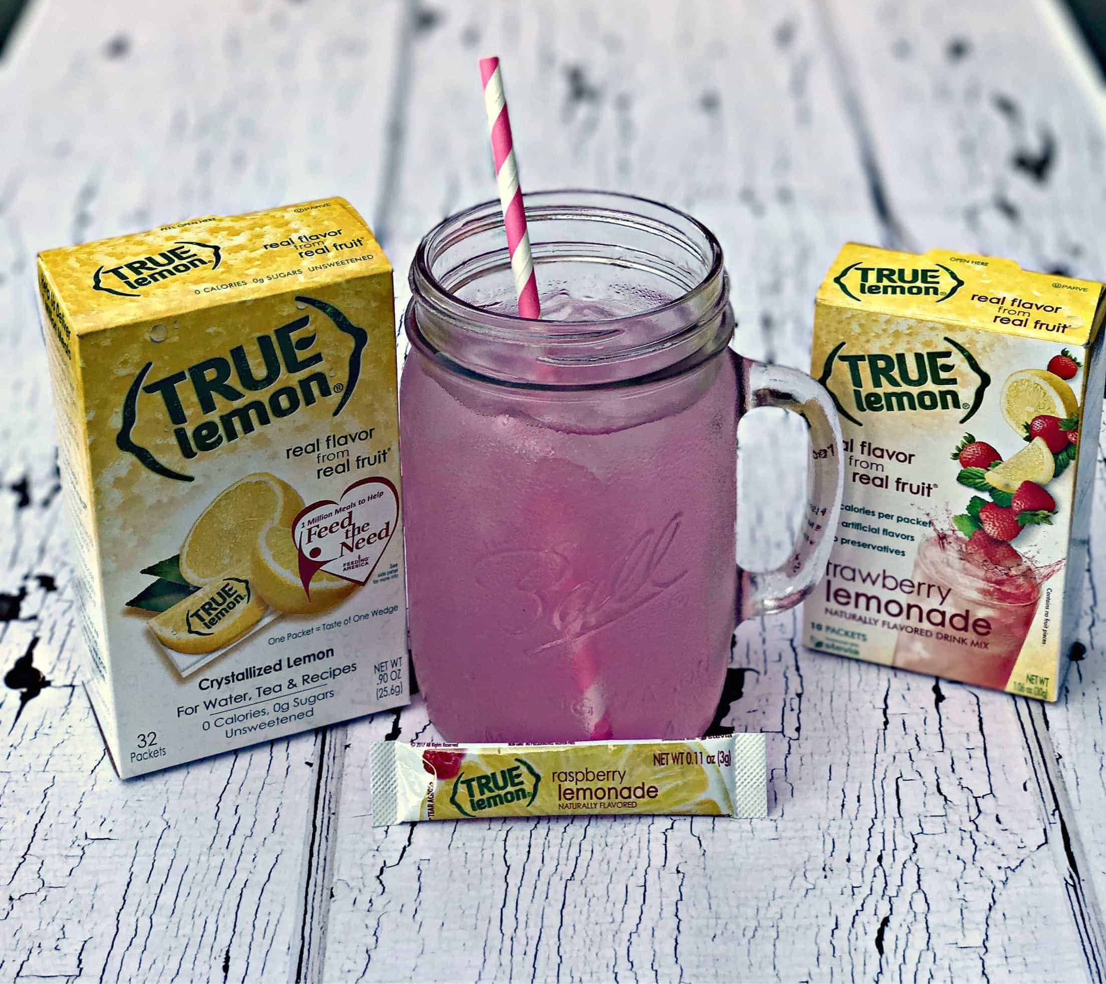 2 boxes of true lemon naturally flavored drink mix, a mason jar with raspberry lemonade and a pink and white straw