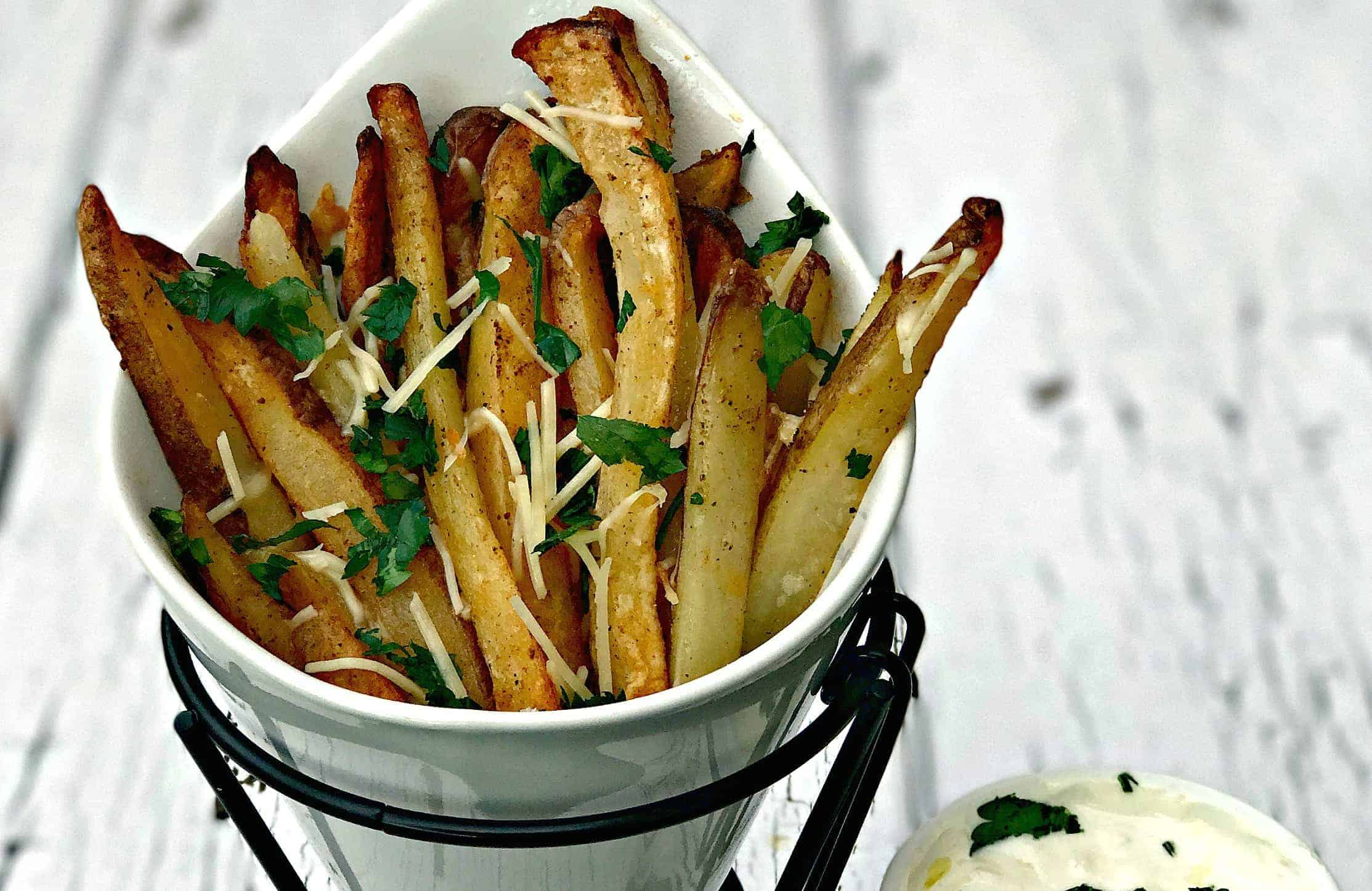 parmesan truffle oil fries in a french fry stand with truffle oil aioli