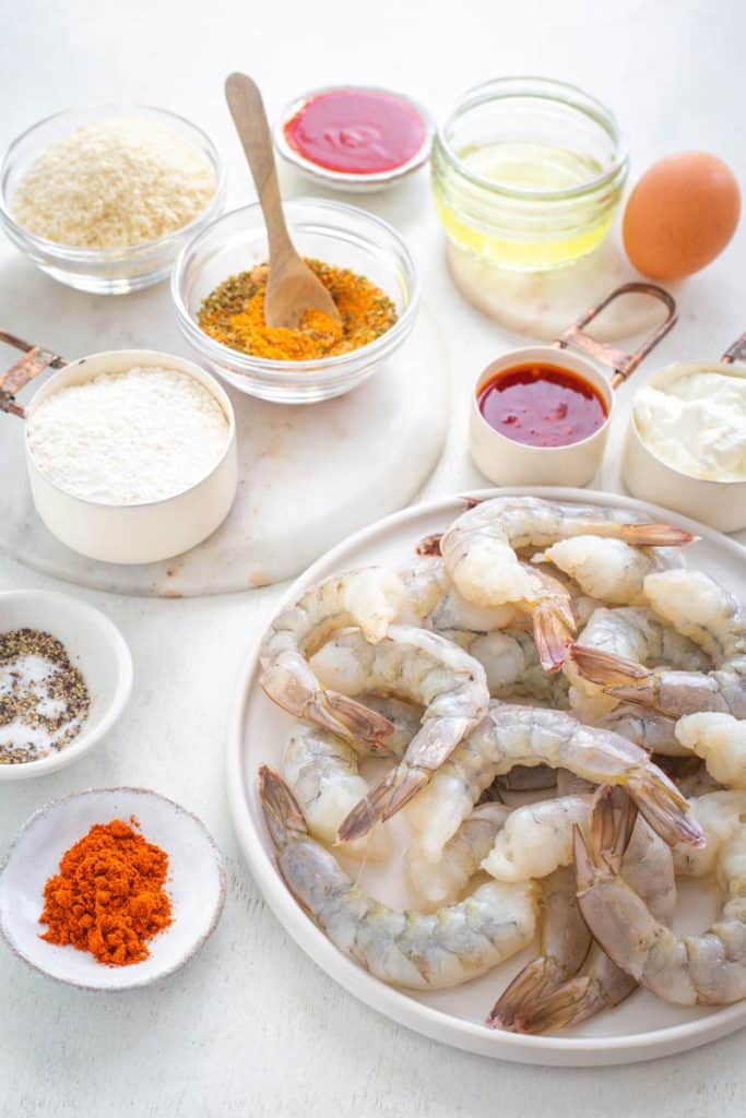 raw shrimp and ingredients for bang bang shrimp on a flat surface