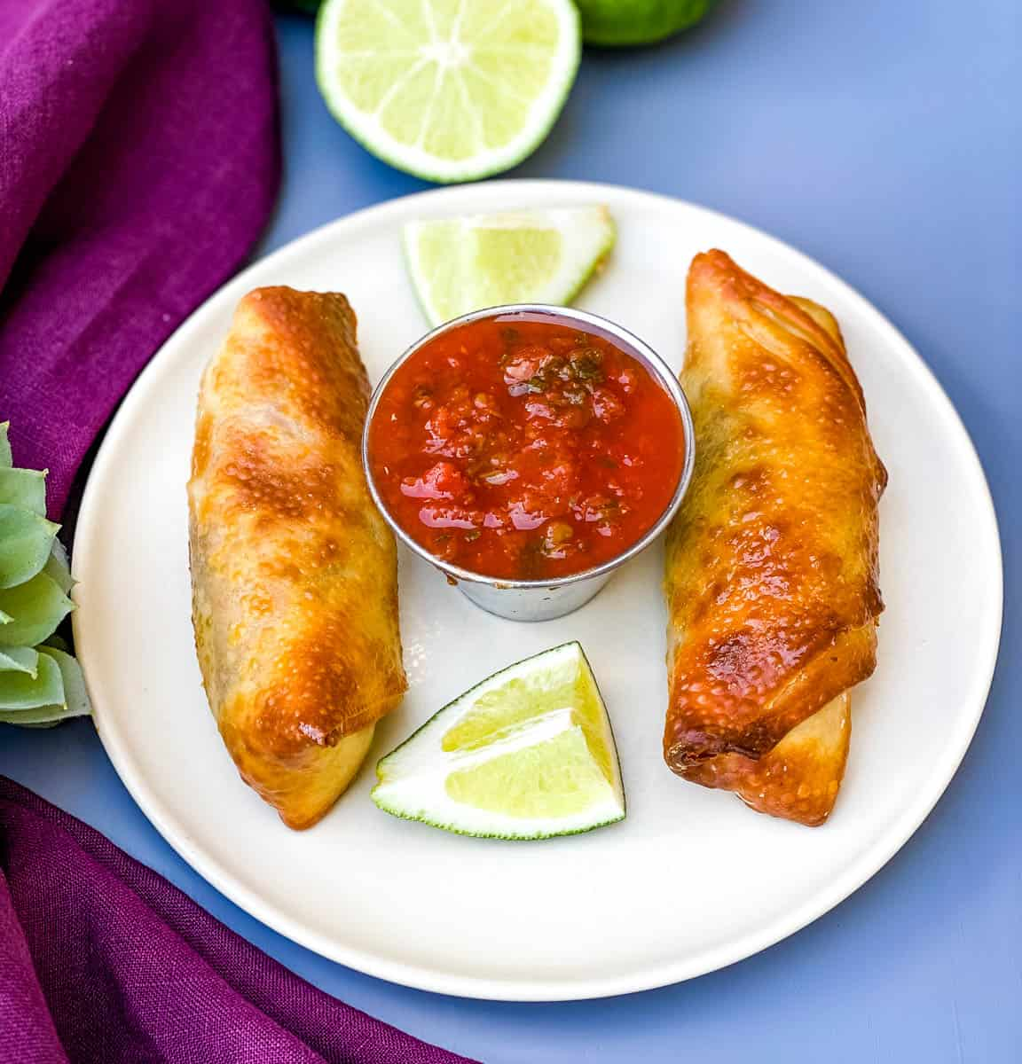 Air Fryer Beef Taco Fried Egg Rolls on a plate with salsa and limes