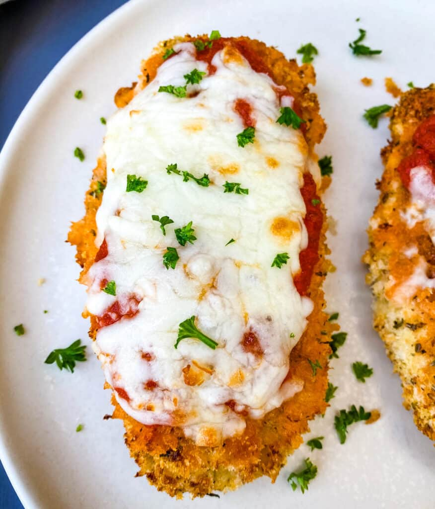 Air Fryer Panko Breaded Chicken Parmesan with Marinara Sauce on a white plate