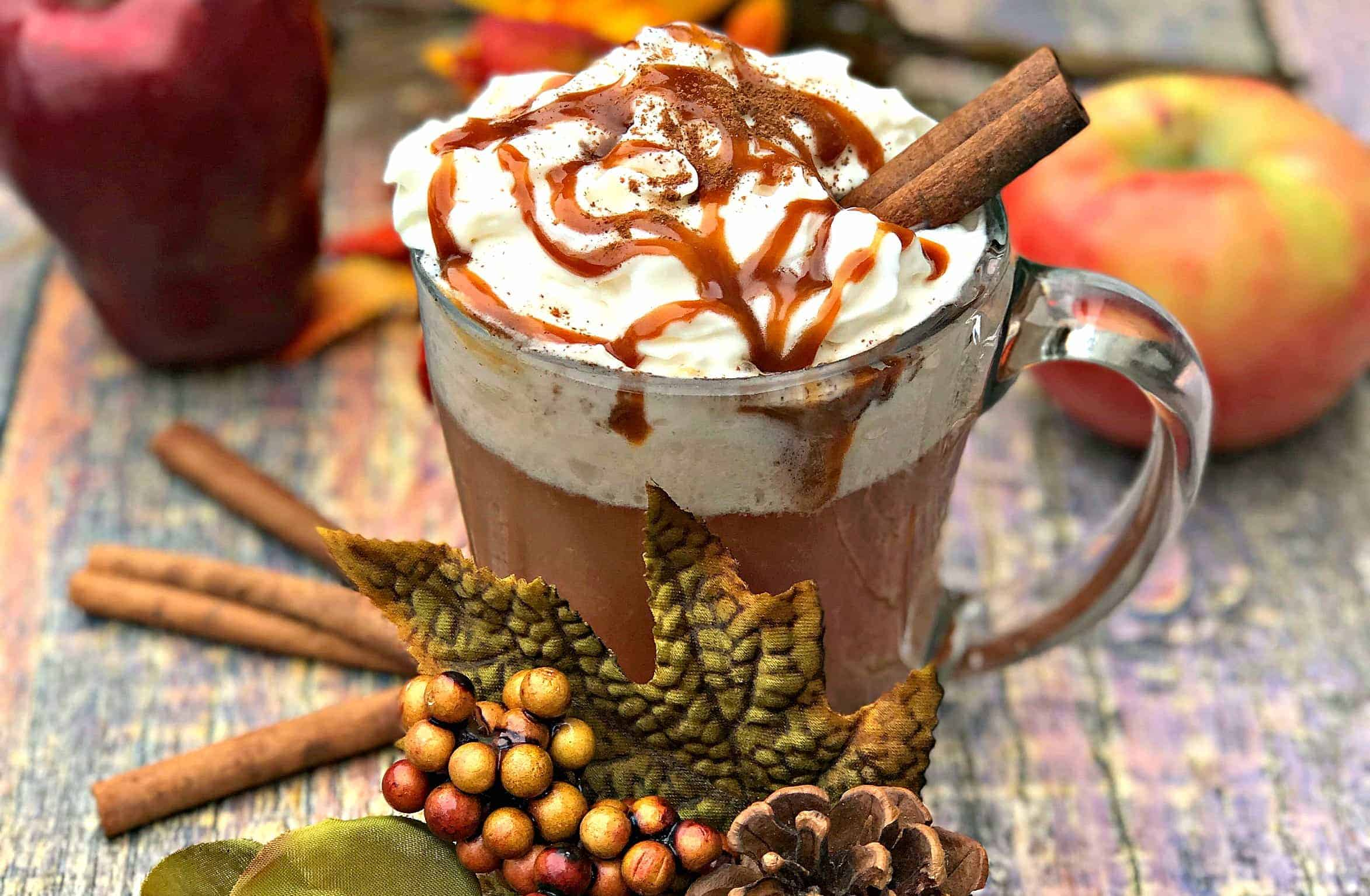 Skinny Copy-Cat Starbucks Caramel Apple Cider in a glass mug with fall decor surrounding the mug