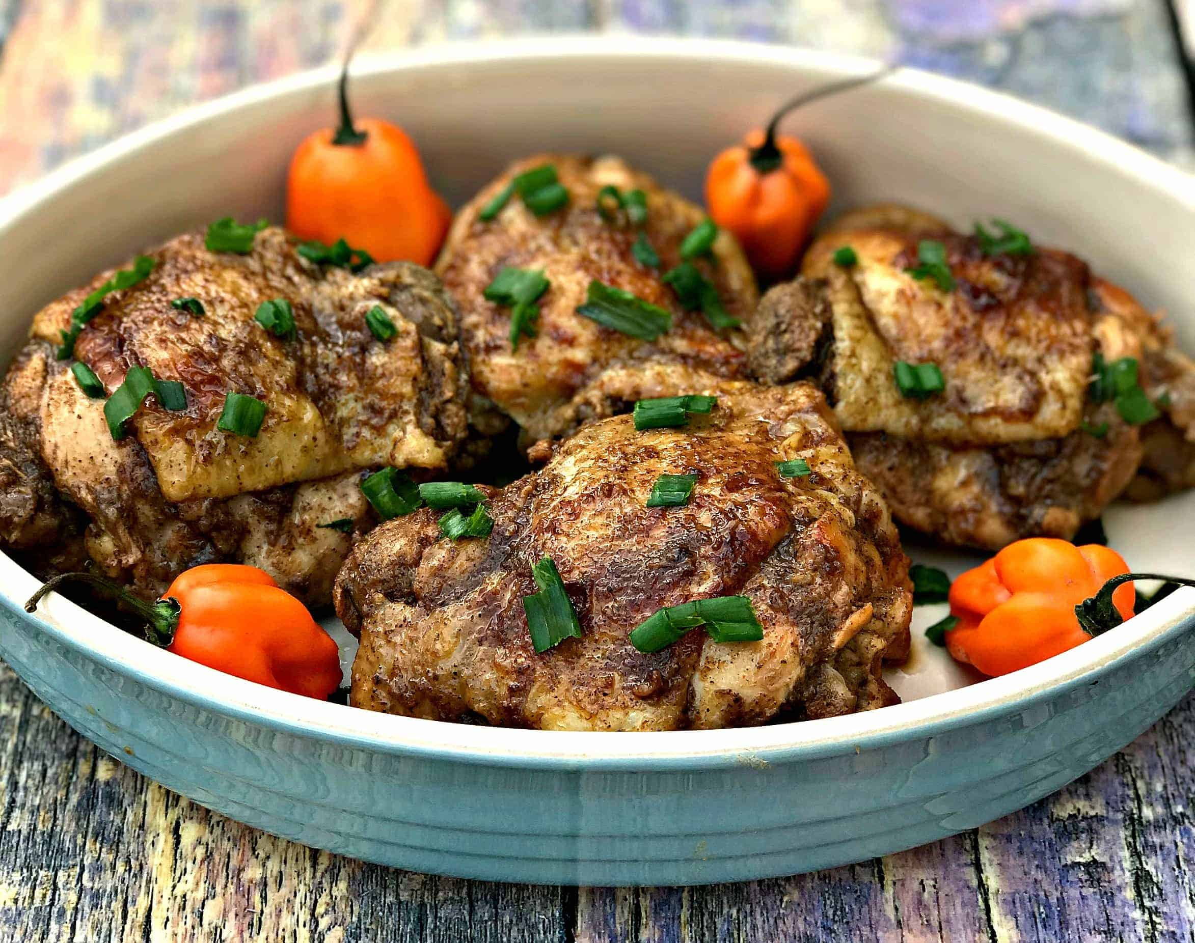 Jamaican jerk chicken thighs on a serving platter garnished with green onions and habanero peppers